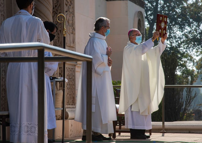 Diocese of Stockton Bishop Myron Cotta, right, conducts the All Souls Day Mass in front of the mausoleum at the Catholic Cemetery in Stockton in 2020.