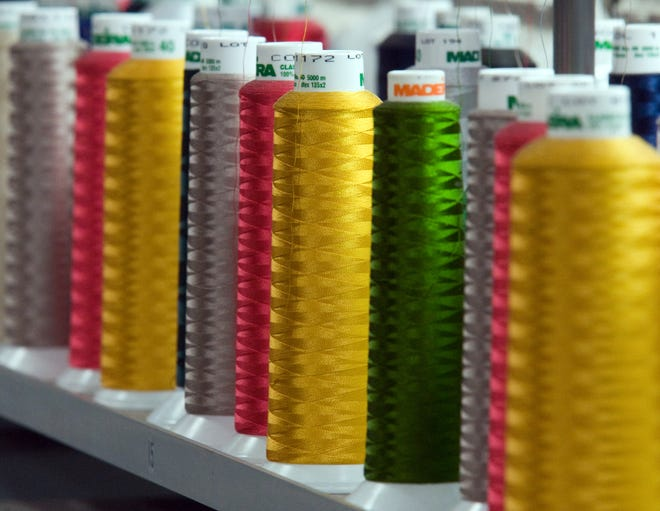 Spools of colored yard on a hat embroidering machine at the Dorfman Pacific Hats in Stockton. More spools are in focus due to a smaller aperture of f/8.
