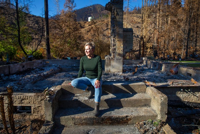 Micki Shampang-Voorhies sits on the front steps of her home in Blue River after it was destroyed by the Holiday Farm Fire.