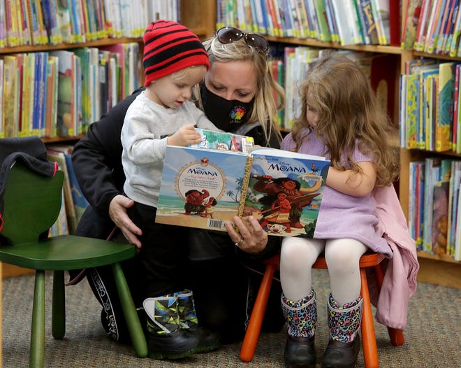 Diane Moser reads to her grandchildren, Beckham Shaffer (2), and Penelope Shaffer (3), in the children's department at the Massillon Public Library. The library sought a renewal levy to help maintain library operations.