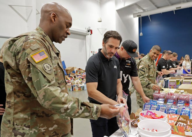 NASCAR driver Jimmie Johnson, second from left, helps assemble care packages for the North Carolina USO during a news conference in Concord, N.C., in 2019. NASCAR's nicest guy will run his final race this week and close a remarkable career. Jimmie Johnson's record-tying seven Cup titles are well celebrated, but his charitable work goes less noticed. The Jimmie Johnson Foundation has donated more than $12 million to schools and programs since it launched.