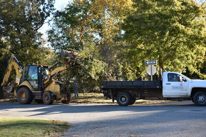 City of Shawnee crews pick up tree debris from Redbud Park Monday.