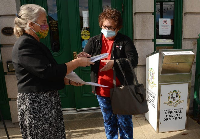 "Betsy Barrett, Norwich city clerk, left, gives an absentee ballot to Enid Rivera of Norwich Monday before Rivera placed her ballot in the drop box at Norwich City Hall. She said she voted for Joe Biden ""To make sure we are treated with respect and dignity."" [John Shishmanian/ NorwichBulletin.com]"