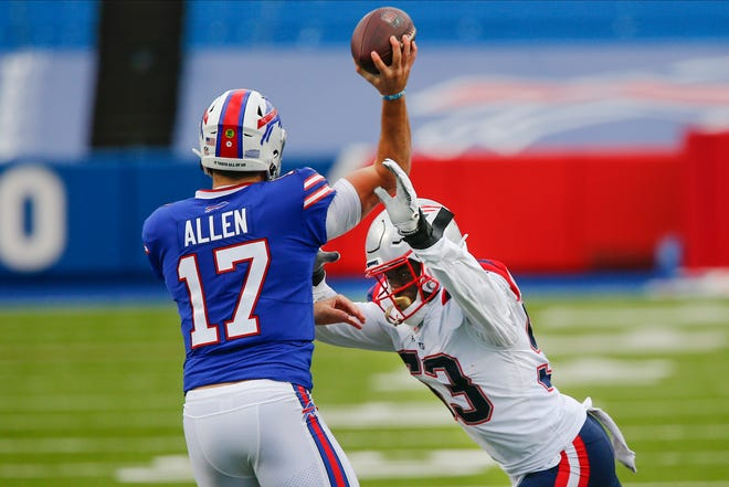 New England's Josh Uche leaps for Buffalo quarterback Josh Allen  during the first half of Sunday's game.