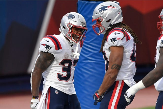 New England running back Damien Harris, left, celebrates with teammate Jakob Johnson after scoring a touchdown during the second half of Sunday's game.