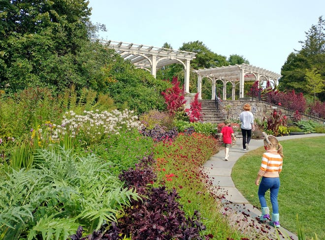 Visitors check out the flowers still in bloom at Tower Hill Botanic Garden earlier this fall.