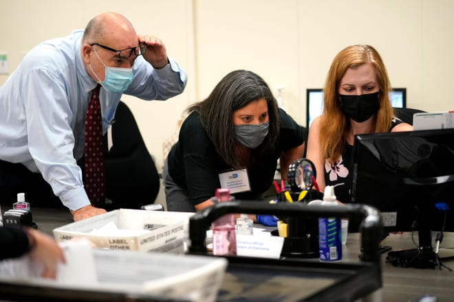 In this Oct. 26 photo, Miami-Dade County Supervisor of Elections Christina White, right, examines signatures on vote-by-mail ballots with members of the county's Canvassing Board.