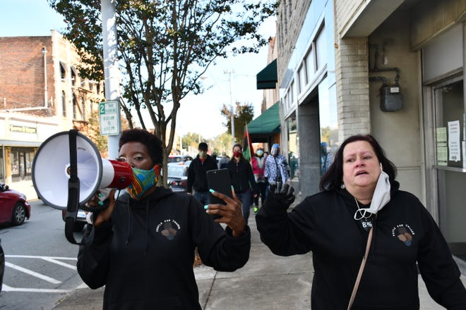 Faith Cook (left) and Ann Jones on Saturday lead a small group of marchers to Graham's early voting precinct on Elm Street. Prior to their impromptu second march, local law enforcement officers ended the initial march and protest by pepper-spraying the crowds and arresting several people. [Photo: Dean-Paul Stephens/Times-News]