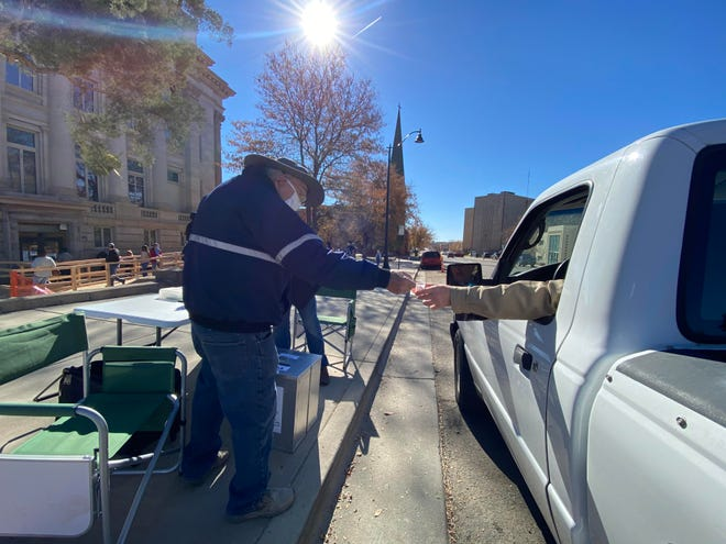 "Lonny Stringer, a Pueblo County election judge hands a citizen an ""I Voted Today"" sticker after the man cast his ballot Monday at a drive-up ballot station on Court Street next to the County Courthouse."