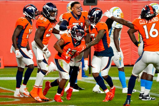 Denver Broncos wide receiver K.J. Hamler (13) celebrates his game-tying touchdown with teammates at the end of regulation against the Los Angeles Chargers on Sunday at Empower Field at Mile High in Denver. The Broncos won 31-30. (AP Photo/Jack Dempsey)