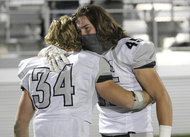 Central's Zeke Healy, left, and C.J. Spinosi console each other after the Warhawks' 38-7 loss at Pickerington Central in the Division I, Region 3 final Oct. 30.