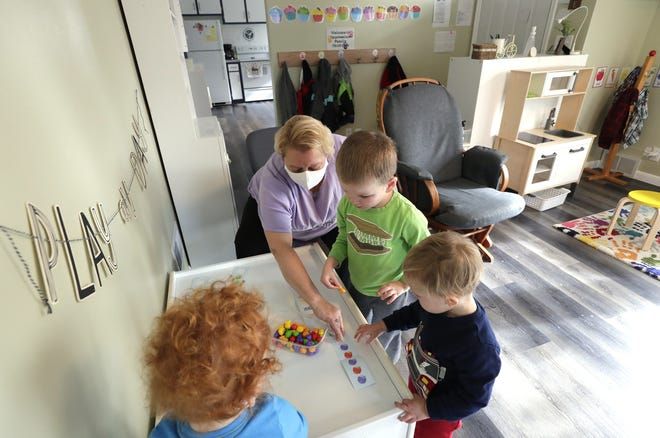 Nicole Leitermann helps Burke Miller, 2, left, Ethan Miller, 3, and Henry McSorley, 2, in a math activity at Impressions Family Child Care Monday, Nov. 2, 2020, in Kimberly, Wis.