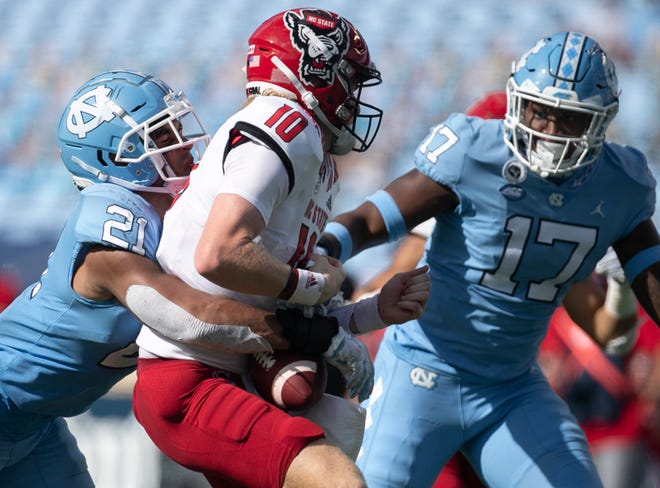 North Carolina's Chazz Surratt (21) sacks N.C. State quarterback Ben Finley (10) for a loss of 14 yards and forces a fumble in the third quarter at Kenan Stadium on Saturday, October 24, 2020 in Chapel Hill, N.C.