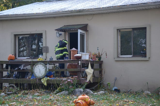 An investigator from the Michigan State Police enters a home Monday damaged by fire.