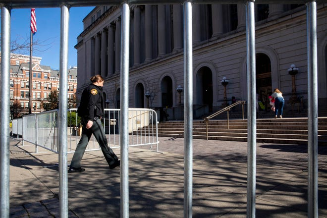 "A Hamilton County Sheriff's Deputy walks through an opening in a barricade that surrounds the Hamilton County Courthouse on Monday, Nov. 2, 2020, in Cincinnati. ""We're simply taking precautions to be prepared in case we see any unrest related to the election,"" spokesman Mike Robison said about the barricade around the courthouse."