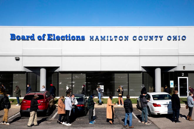 Voters wait in line on the last day of early voting outside the Hamilton County Board of Elections in Norwood on Monday, Oct. 2, 2020.