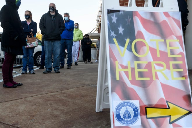 People wait in a long line outside of Old National Events Plaza in Downtown Evansville, Ind., to cast an early ballot, Monday morning, Nov. 2, 2020. The Old National Events Plaza was the only early polling site open Monday, from 8 a.m. to noon, with many voters waiting between one to two hours to cast their ballots.