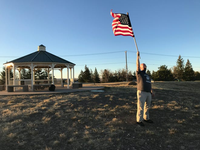 Luke Skinner waves the flag in Warden Park overlooking the city of Great Falls Monday morning.