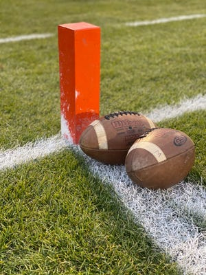 Footballs sit on the field next to a pylon prior to a football game.