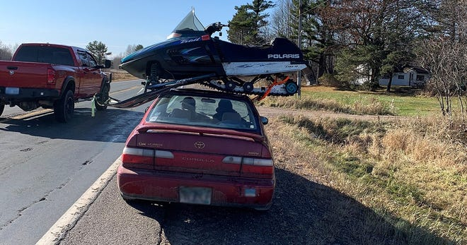 The Wisconsin State Patrol pulled over a driver who was transporting a snowmobile on the roof of a Toyota Corolla.