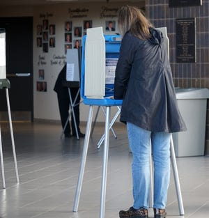 A voter uses a kiosk to fill out her absentee ballot on Novi. 2, 2020, at the Novi Civic Center.