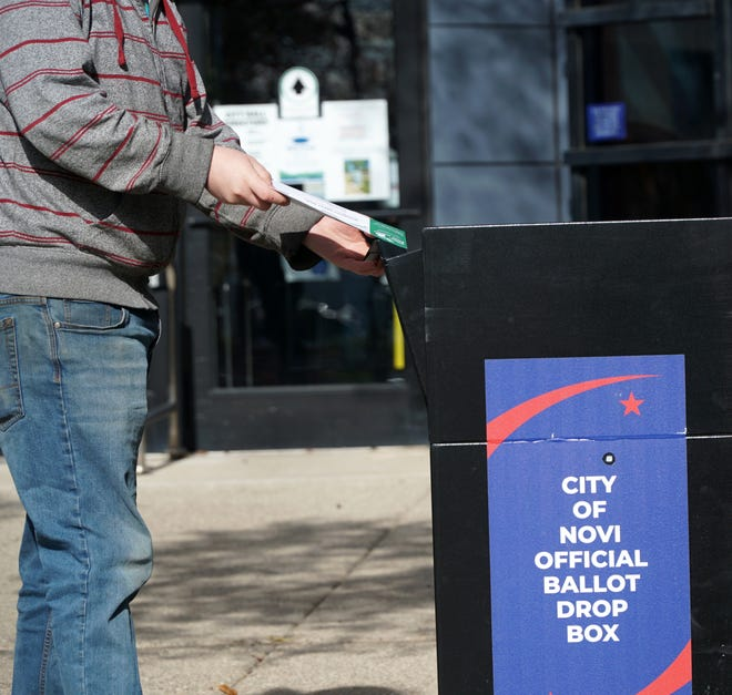 A voter drops their ballot in Novi's absentee ballot box outside the Novi Civic Center on Nov. 2, 2020. On Nov. 2, 2021, voters can go to the polls (or vote absentee beforehand again) to elect one of two candidates for Novi mayor to a 2-year term.