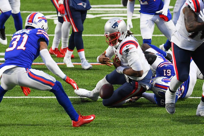 Nov 1, 2020; Orchard Park, New York; New England Patriots quarterback Cam Newton (1) fumbles the ball as he's hit by Buffalo Bills defensive tackle Justin Zimmer (61) in the fourth quarter at Bills Stadium