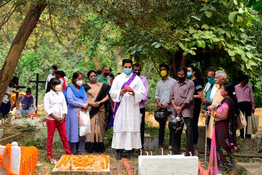 A Christian priest (C) offers prayers during All Souls Day at Rajapur Cemetery in Allahabad on November 2, 2020.