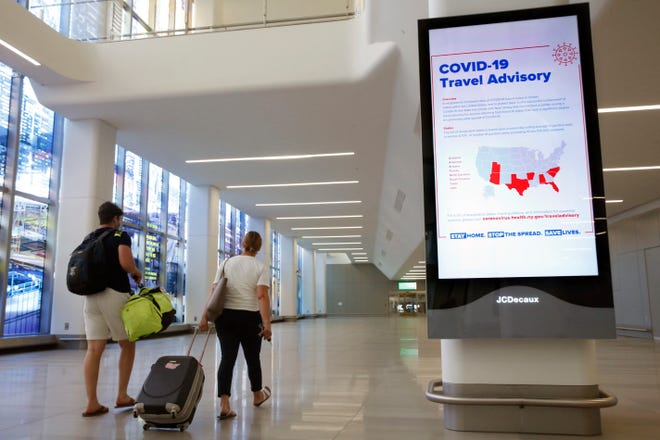 Arriving travelers walk by a COVID-19 travel advisory sign at New York City's LaGuardia Airport in this June 25 file photo.