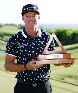 Brian Gay, a former standout at the University of Florida, celebrates with the trophy Sunday after winning during a playoff in the final round of the Bermuda Championship at Port Royal Golf Course on in Southampton, Bermuda.
