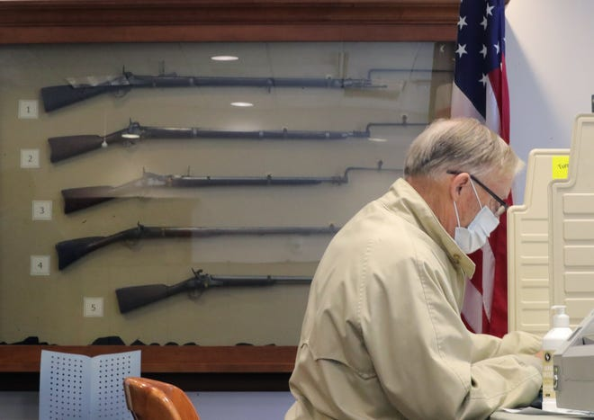 Hudson resident Tom Murdough casts his vote at the Hudson Library polling station on Tuesday.