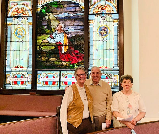 """The United Methodist Church of Jeromesville celebrated their 200th anniversary on Oct. 18. History and memories were shared by several members at different times throughout 2020. The October service involved members of the Youth and the congregation, along with a past minister, as they celebrated by """"Praising God for 200 years.""""  Shown in the photograph in front of one of the two stained-glass windows in the church are Beryl Baum, minister from 2000-2004, Lowell McFarlin, 75-plus year member, and Nancy Kline, 50-plus year member. JUMC is well known for its 62-plus years of service at its Ashland County Fair food tent, hard tack candy-making and additional mission work completed both locally and worldwide."""