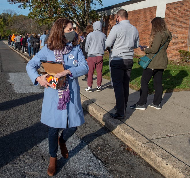 Democratic Congressional candidate Christina Finello,  hands out hand warmers to voters waiting in line outside the Neil Armstrong Middle School, in Fairless Hills, on Tuesday, Nov. 3, 2020.