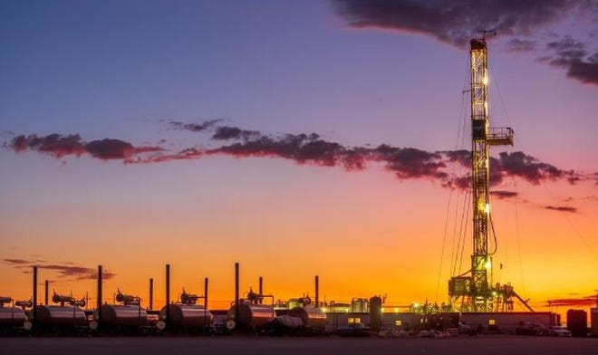 A sunrise illuminates a drilling and production location in the Delaware Basin owned by WPX Energy.