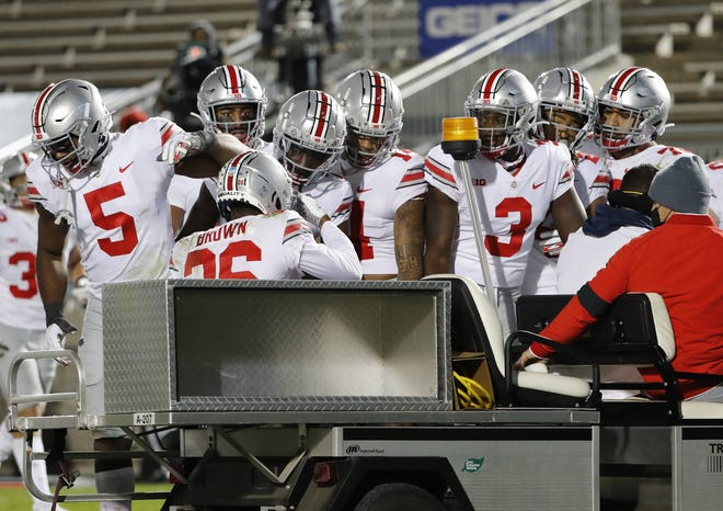 Teammates check on Ohio State defensive back Cameron Brown as he was carted off the field after suffering an Achilles injury late in Saturday's win against Penn State.