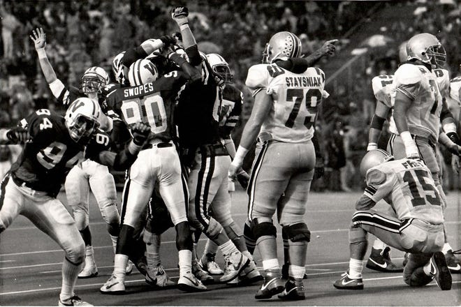 Ohio State quarterback Greg Frey (15) kneels in dejection after his fourth-quarter interception sealed the Buckeyes' 26-24 loss to Wisconsin in 1987.