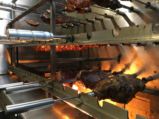 A trough of wood burns under skewered meats and poultry at the Brazilian Grill in Hyannis. There are several cuts of beef, including flank steak and top sirloin, as well as a traditional Brazilian cut.
