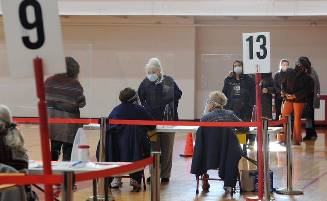 Poll workers protected by sheets of plastic check in voters at the Hyannis Youth and Community Center.