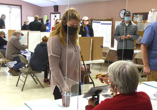 Election judge Lane Recker instructs Megan Early on how to sign in during voting on Tuesday at the University of Missouri Extension center at 1012 N. Highway UU. More than 500 people had voted there by 10:47 a.m.