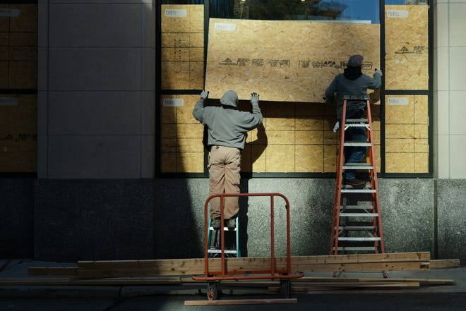 Workers board up windows on the Ohio Chamber of Commerce Building on South Third Street in preparation of potential unrest because of the election.