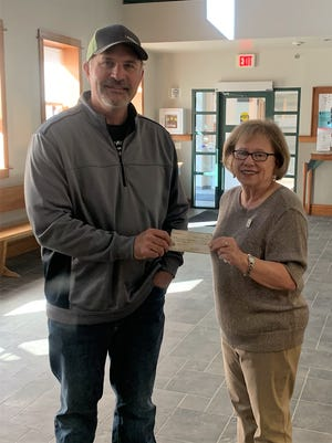 Parks and Recreation Director Nick Schenck receives a donation from Women's Club representative, Mary Ockerman.