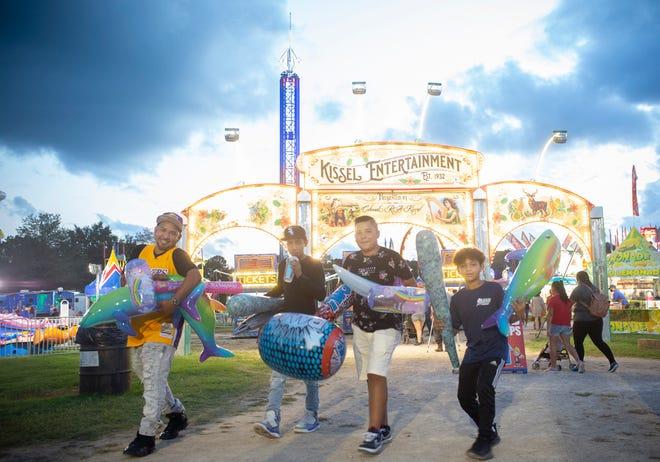 David Mora, Xavier Mora, 14, Anthony Mora, 12, andIvan Mora, 12 celebrate a successful day at the Maury County Fair and Exposition held at the Maury County Park in Columbia, Tenn., on Thursday, Sept. 3, 2020.