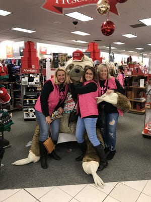 Annette Kruse (left) and her aunts, Troi Ann Michael and Sarah Ratliff, joke around with a giant, stuffed sloth at Kohl's during their 2019 Black Friday shopping trip together. Ratliff gifted the trio the matching, pink vests to go with the matching 'Black Friday Shopping Crew' t-shirts Kruse provided a year earlier so they could easily find each other if they were separated in the crowds on Black Friday.