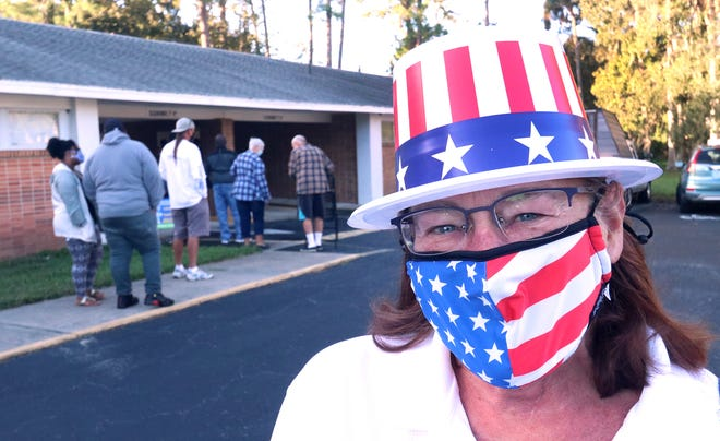 Campaign worker Lesley Coffrin is adorned with patriotic hat and mask as a line of voters inches along in the background at Church of Christ on Beville Road in Daytona Beach.