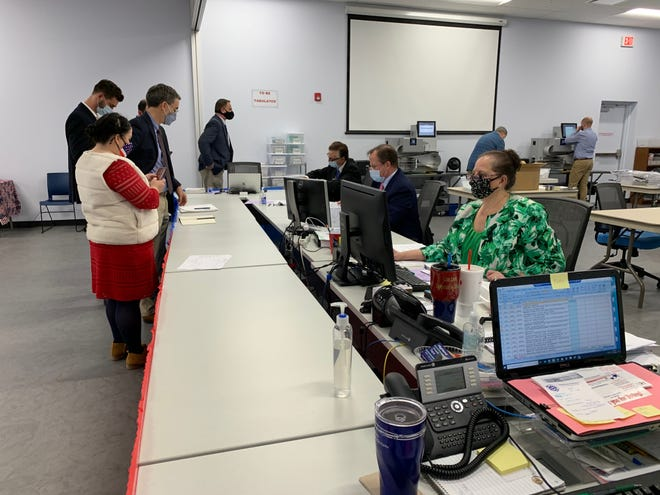 Supervisor of Elections Lisa Lewis, right, in green, and the canvassing board get down to counting ballots at the DeLand office on Tuesday, Nov. 3, 2020.