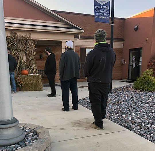 Voters wearing masks and social distancing line up about 7:45 a.m. Tuesday outside the Shenango Township Municipal Building in Lawrence County.