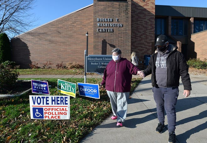 Charmaine Alexander of Erie is assisted by Kevin Hertzog of New York City on Tuesday outside the Booker T. Washington Center in Erie. Hertzog, who traveled to Erie to drive voters to the polls, was taking Alexander from the Booker T. Washington Center to the Morning Star Baptist Church in Erie after she discovered she was at the wrong voting location.