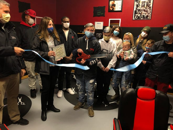 Tosha Smith, popularly known as Tmac the Barber, holds a pair of scissors after cutting a ribbon Monday morning to open her new business, the Faded Barbershop at 200 Canisteo St. in Hornell. Family, friends, colleagues and Hornell Partners for Growth officials surround Smith as she realizes her long-time dream of opening a barbershop.