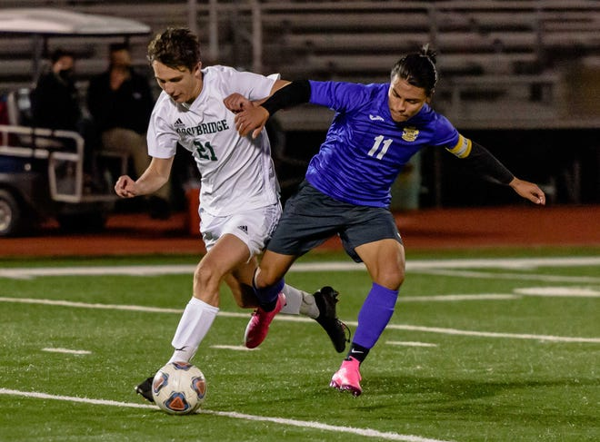 Blue Springs' Matthew Martinez (11) and Columbia Rock Bridge's Andrew Copeland fight for possession in their Class 4 District 9 semifinal Monday at Columbia Hickman High School. Martinez scored on a free kick as time expired to lift the Wildcats to a 2-1 victory.