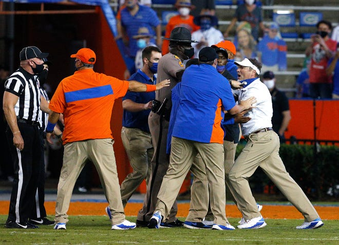 Florida coach Dan Mullen, right, is held back by coaches and law enforcement after a fight broke out at the end of the first half of the team's game against Missouri Saturday in Gainesville, Fla., Mullen was fined $25,000 for his role in the incident.